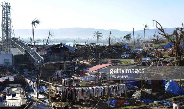Clothes hang next to destroyed houses and toppled trees in Cateel town Davao Oriental province on December 11 2012 in the aftermath of Typhoon Bopha...