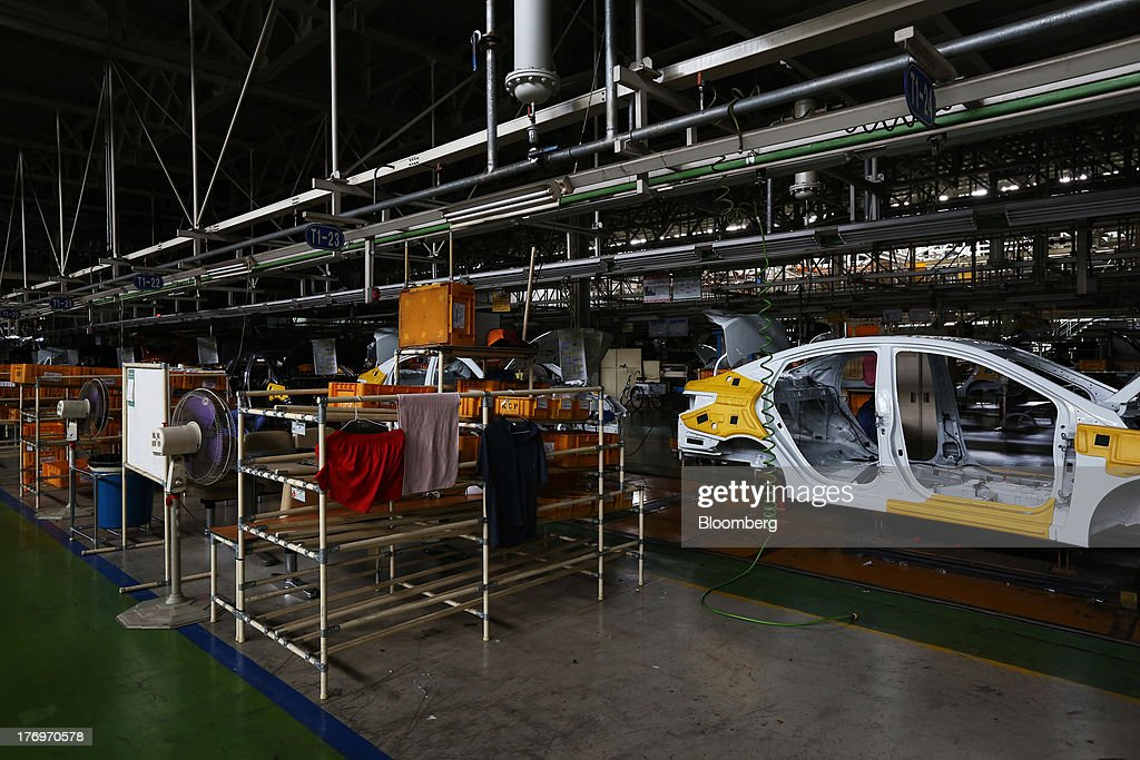 Clothes hang on a rack as vehicles stand on the halted assembly line at the Hyundai Motor Co. plant during a strike by the company's labor union in Ulsan, South Korea, on Tuesday, Aug. 20, 2013. Union members at Hyundai Motor, South Korea's largest automaker, staged a partial strike today that will continue tomorrow as they demand higher wages amid increasing competition with Japanese carmakers. Photographer: SeongJoon Cho/Bloomberg via Getty Images
