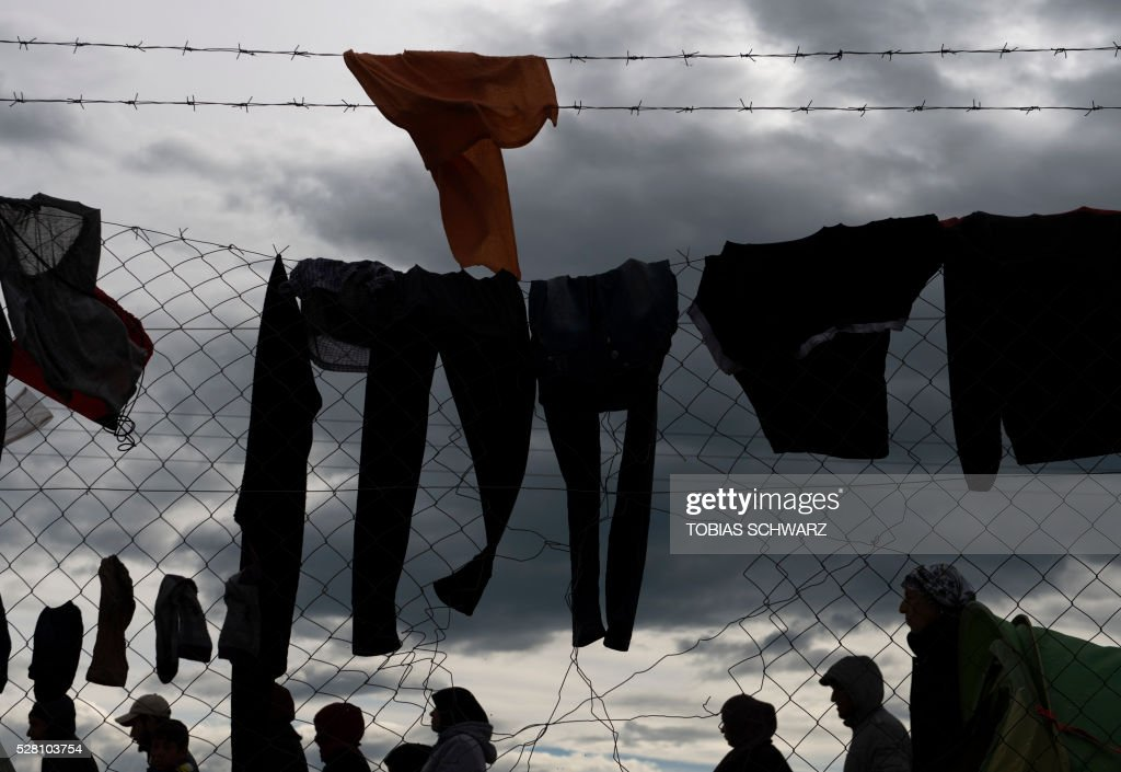 Clothes hang to dry at a makeshift camp for migrants and refugees near the village of Idomeni not far from the Greek-Macedonian border on May 4, 2016. Some 54,000 people, many of them fleeing the war in Syria, have been stranded on Greek territory since the closure of the migrant route through the Balkans in February. / AFP / TOBIAS