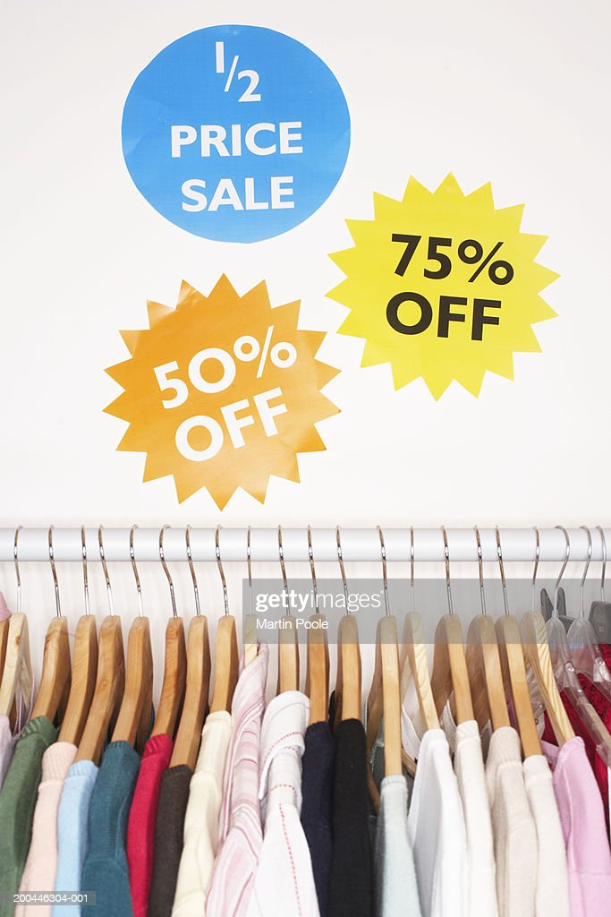 Clothes hanging on rail, sale signs on wall