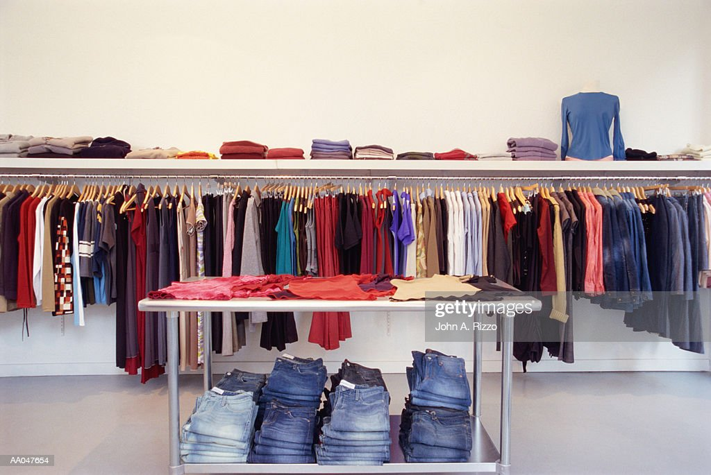 Clothes on rack and table in store : Stock Photo