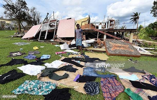 Clothes sit on the ground to dry as Adrian Banga stands in front of his destroyed house on March 16 2015 in Port Vila Vanuatu Cyclone Pam has hit...