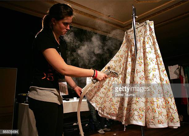 A clothing assistant steams a dress backstage during the New Order fashion show during Motorola Melbourne Spring Fashion Week at the Melbourne Town...