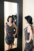 Happy mid adult woman wearing a stylish dress standing in front of mirror with hands on hips in boutique