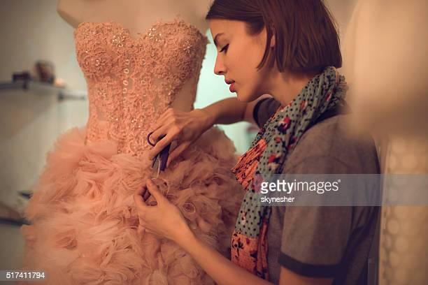 Vestuário Designer de material de corte em um vestido em curso.