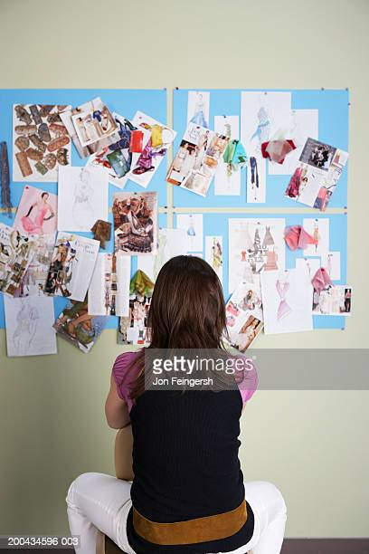 Clothing designer looking at sketches, rear view