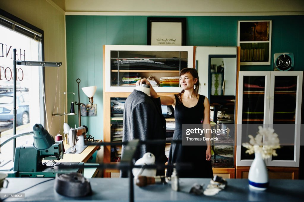 Clothing designer looking out studio window : Stock Photo