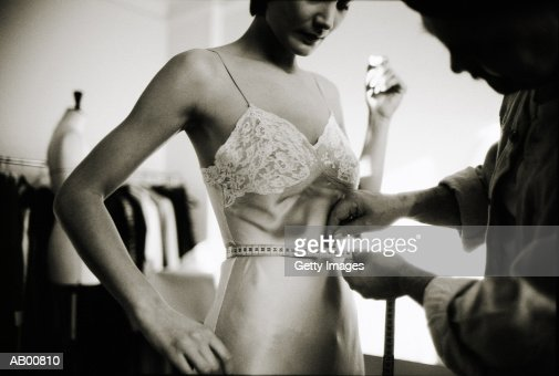 Clothing designer measuring waist of female client (B&W) : Stock Photo