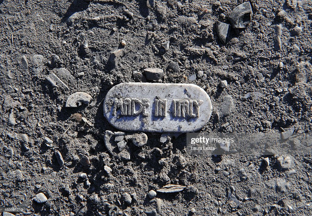 A clothing label with the inscription 'made in italy' is seen on the ground next to the clothing factory after the fire where seven Chinese workers died burned alive on December 4, 2013 in Prato, Italy. Last sunday seven people died and three were injured when a Chinese clothing factory in the industrial district of the Italian town of Prato in Tuscany burned down, killing the workers trapped in the dormitory built in there. Chinese workers sleep, eat, live and work in the same factory all day. In Prato, Chinese companies are over 5,000 and almost none of them is in compliance with the law and workers working 16 hours of day and night,for one euro per hour.