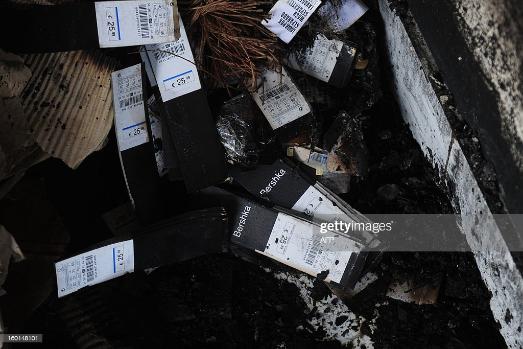 Clothing labels from 'Bershka' lie amongst devastation after a fire swept though the garment factory in Dhaka on January 27, 2013. At least seven female workers were killed on January 26 after a blaze swept through a small garment factory in the Bangladeshi capital of Dhaka, police and fire officials said. AFP PHOTO / Munir uz ZAMAN