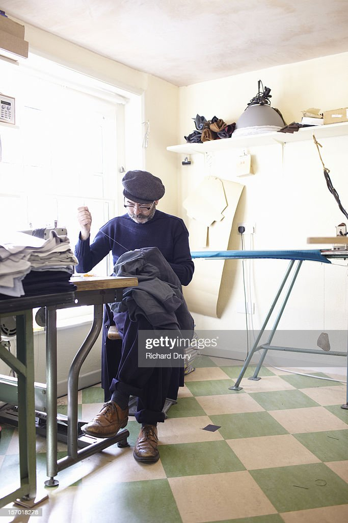 clothing manufacturer sewing in his workshop : Stock Photo
