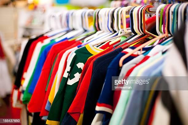 Rack abbigliamento completo di T-shirt in un negozio di articoli di seconda mano