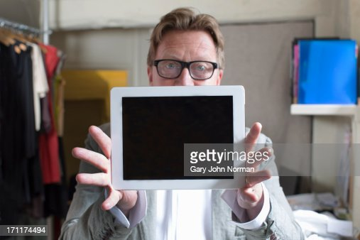 clothing shop manager holding  ipad in front : Foto de stock