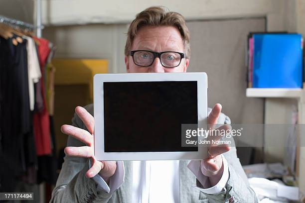 clothing shop manager holding  ipad in front
