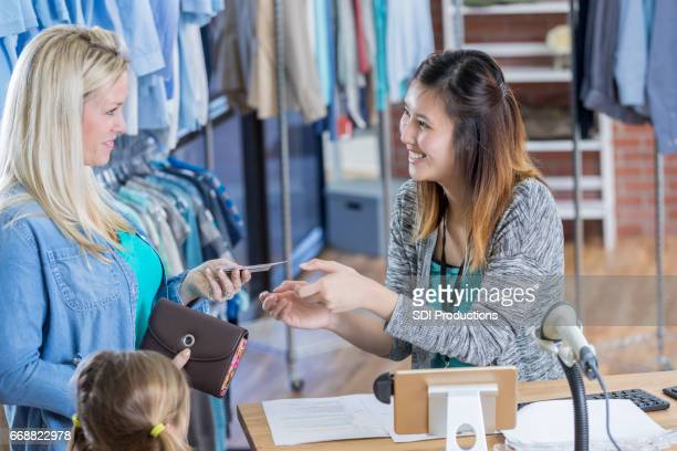 Clothing store customer gives credit card to cashier
