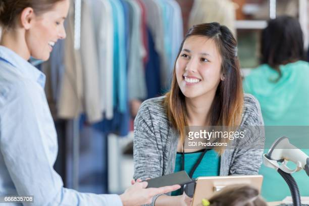 Clothing store customer uses smart phone to pay for purchase