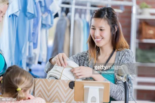 Clothing store employee helps customer