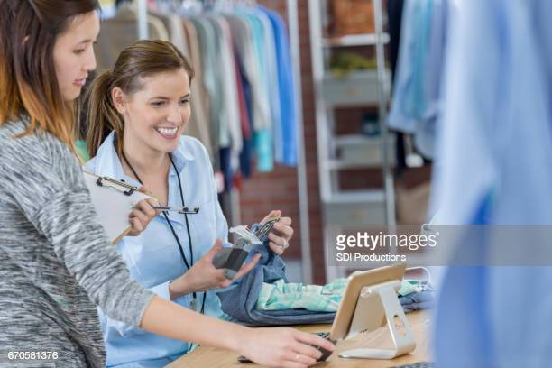 Clothing store employees work together at cash register