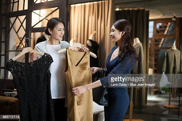 Clothing store owner showing customer dresses