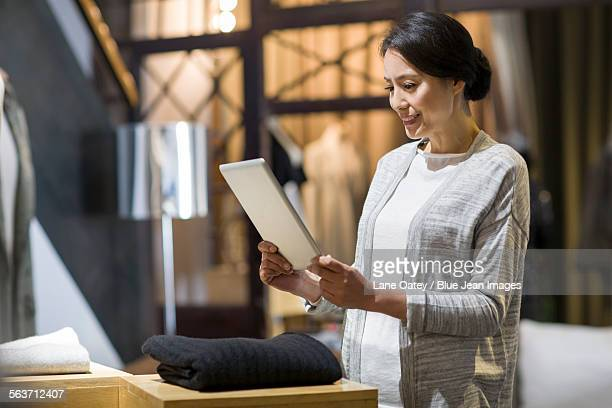 Clothing store owner with digital tablet