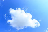 Lonely white fluffy cloud in the light blue sky background on sunny day