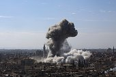A cloud of smoke rises following an air strike by Syrian government forces in the rebelheld area of Douma north east of the capital Damascus on...