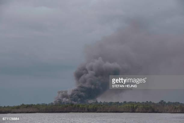 A cloud of smoke rises from an illegal oil refinery on April 19 2017 in the Niger Delta region near the city of Port Harcourt NNS Delta of the...