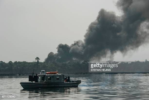 A cloud of smoke rises from an illegal oil refinery on April 19 2017 in the Niger Delta region near the city of Port Harcourt NNS Pathfinder of the...