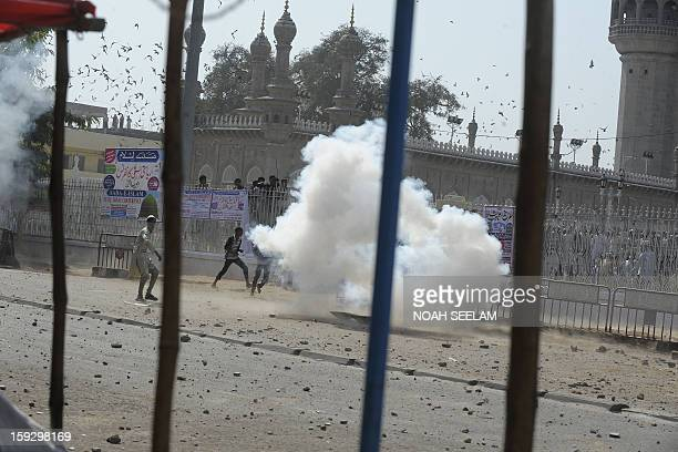 A cloud of tear gas forms as supporters of the MajliseIttehadul Muslimeen clash with police outside the historic Mecca Masjid following...