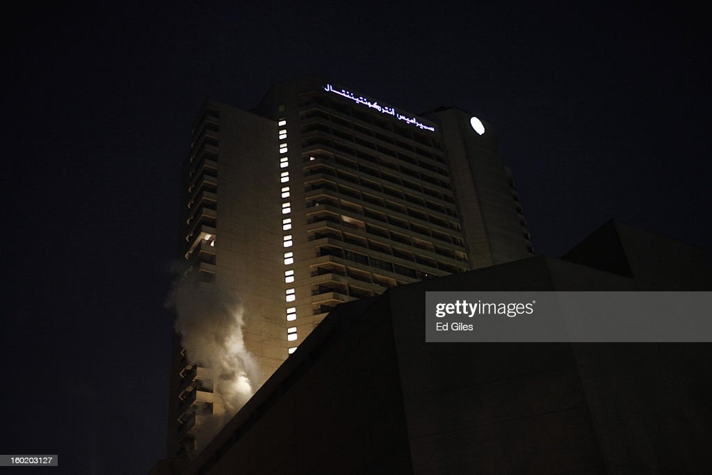 A cloud of tear gas rises from a balcony of the luxury Intercontinental Hotel after a canister fired by Egyptian riot police landed on the building during clashes with Egyptian protesters near Tahrir Square on January 27, 2013 in Cairo, Egypt. Violent protests continued across Egypt two days after the second anniversary of the Egyptian Revolution that overthrew former President Hosni Mubarak on January 25, and one day after the announcement of the death penalty for 21 suspects in connection with a football stadium massacre one year before. The verdict was announced in a case over the deaths of more than seventy fans of Egypt's Al-Ahly football club in a stadium massacre on February 1, 2012, in the northern city of Port Said, during a brawl that began minutes after the final whistle of a match between Al-Ahly and opposing side, Al-Masry. 21 fans of the opposing side, Al-Masry, were given the death penalty, a verdict that must now be approved by Egypt's Grand Mufti. (Photo by Ed Giles/Getty Images).