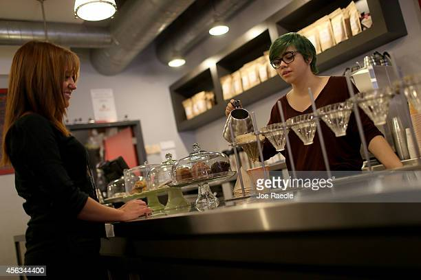Cloud Perez Vento pours a slowbrew process coffee for Maria Escorcia at Eternity Coffee Roasters during National Coffee Day on September 29 2014 in...