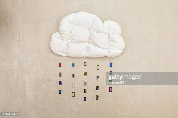 Cloud shape pillow with mobile phones forming rain on beige background