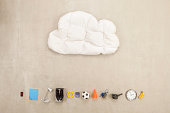 Cloud shape pillow with variety of items on beige background