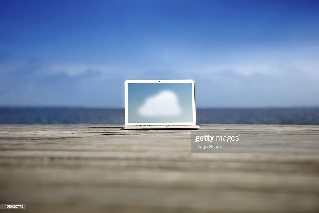 Cloud symbol on a laptop on a pier : Stock Photo