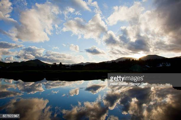 Clouds and blue sky reflected in the tranquil water of Sneem Harbour
