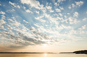 Beautiful clouds and sun rays over lake at sunrise