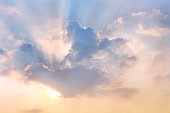 Clouds and sun shines through rays of light in the illuminated picturesque sky.