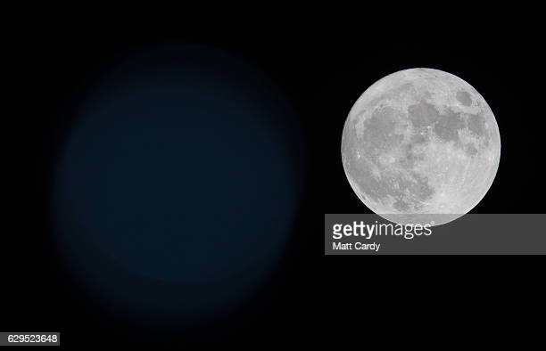 Clouds clear to allow a view of the final full moon of the year a socalled 'Cold Moon' as it appears behind lights illuminating Penzance seafront on...