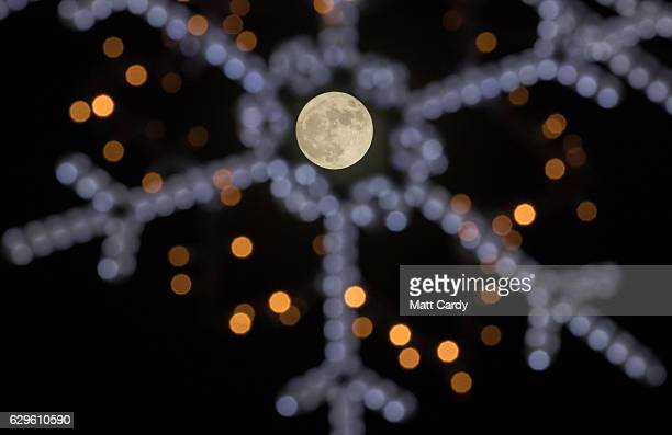 Clouds clear to allow a view of the final full moon of the year a so called 'Cold Moon' as it appears behind Christmas lights decorating Penzance...
