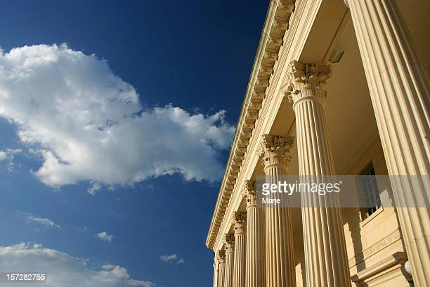 Clouds drifting above golden columns across a blue sky