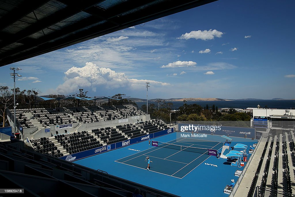 Clouds from a nearby bushfire are seen as play continues on centre court during day one of the Hobart International at Domain Tennis Centre on January 4, 2013 in Hobart, Australia.