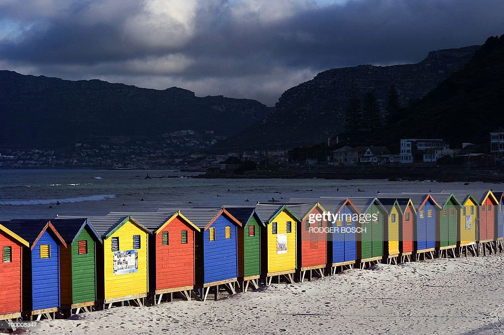 Clouds gather as surfers take on the ocean close by coloured bathing huts on May 19, 2010 at the Muizemberg beach on the outskirts of Cape Town, South Africa. South Africa will host the FIFA World Cup from the 11 of June to the 11 of July, 2010.