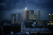 Clouds gather over highrise buildings in the financial district of the Canary Wharf area of East London as workers remain in their offices as the day...