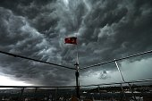Clouds gather over the Bosphorus behind a Turkish flag during a storm on August 7 in Istanbul AFP PHOTO/OZAN KOSE