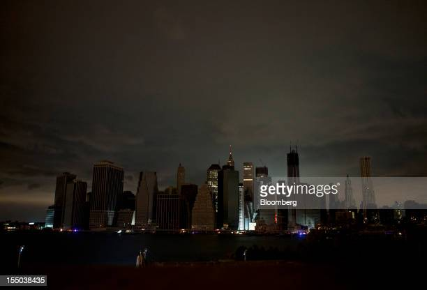 Clouds hang over the darkened lower Manhattan skyline at night in New York US on Tuesday Oct 30 2012 New York City officials spent the day grappling...