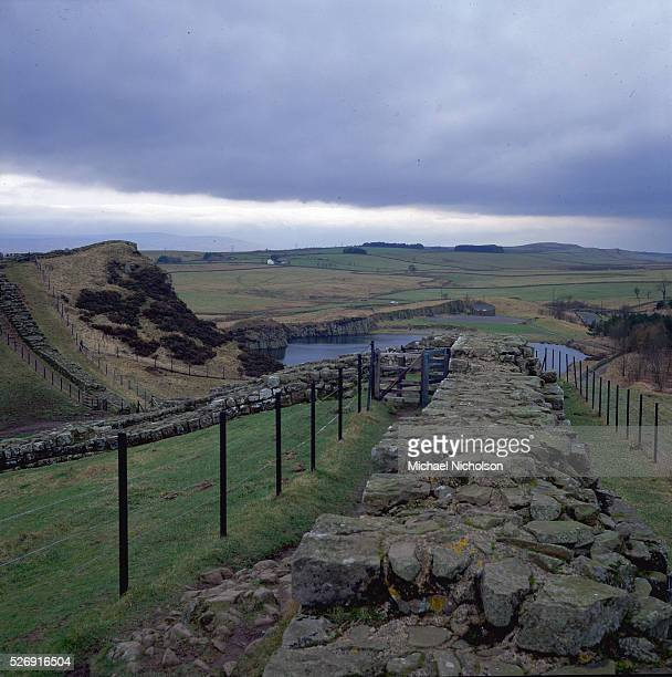 Clouds loom above undulating pastures overlooked by a section of Hadrian's Wall at Cawfields in Northumberland England Begun around 122 AD the wall...