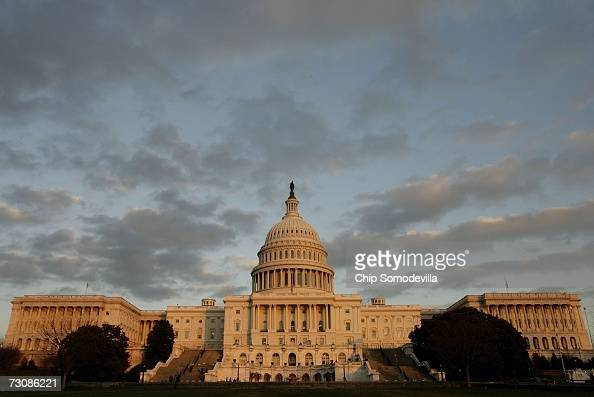 Clouds move as the sun sets against the west front of the United States Capitol building January 23 2007 in Washington DC US President George W Bush...