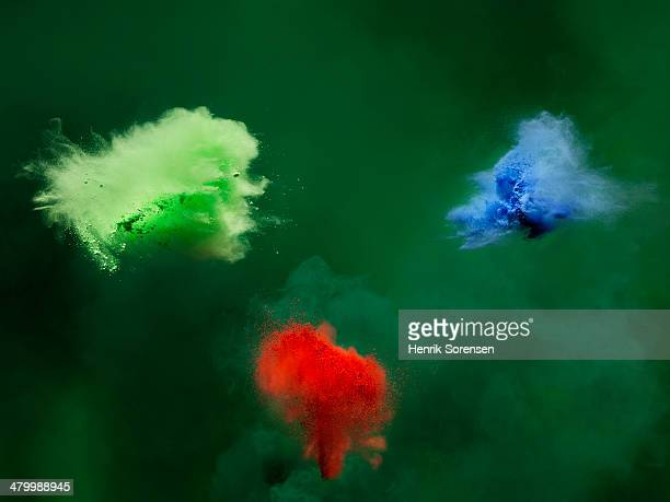 3 clouds of colored powder