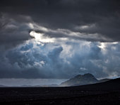 Clouds over mountains and black sands.