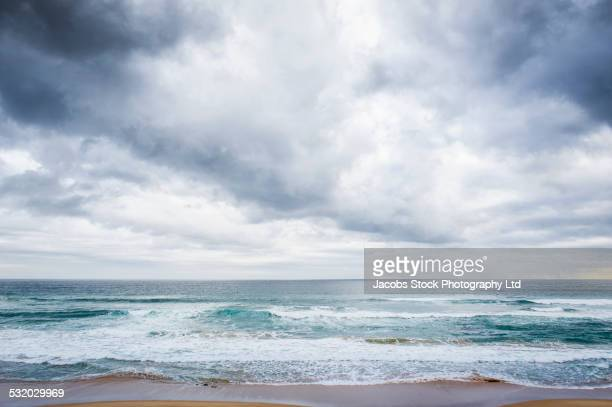 Clouds over ocean waves on beach